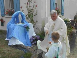 L'abbé Pierre Bizet, curé de la paroisse, bénit la vierge du reposoir chez Monique Courmont (r)